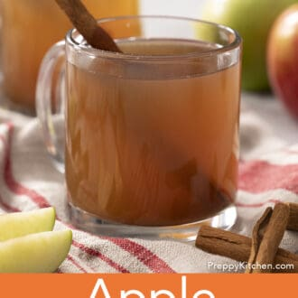 A glass mug of apple cider on a brown and red linen napkin.
