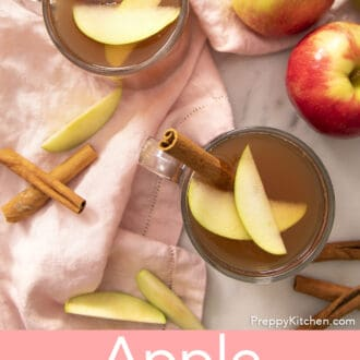A top-down view of glass mugs filled with apple cider next to apples.