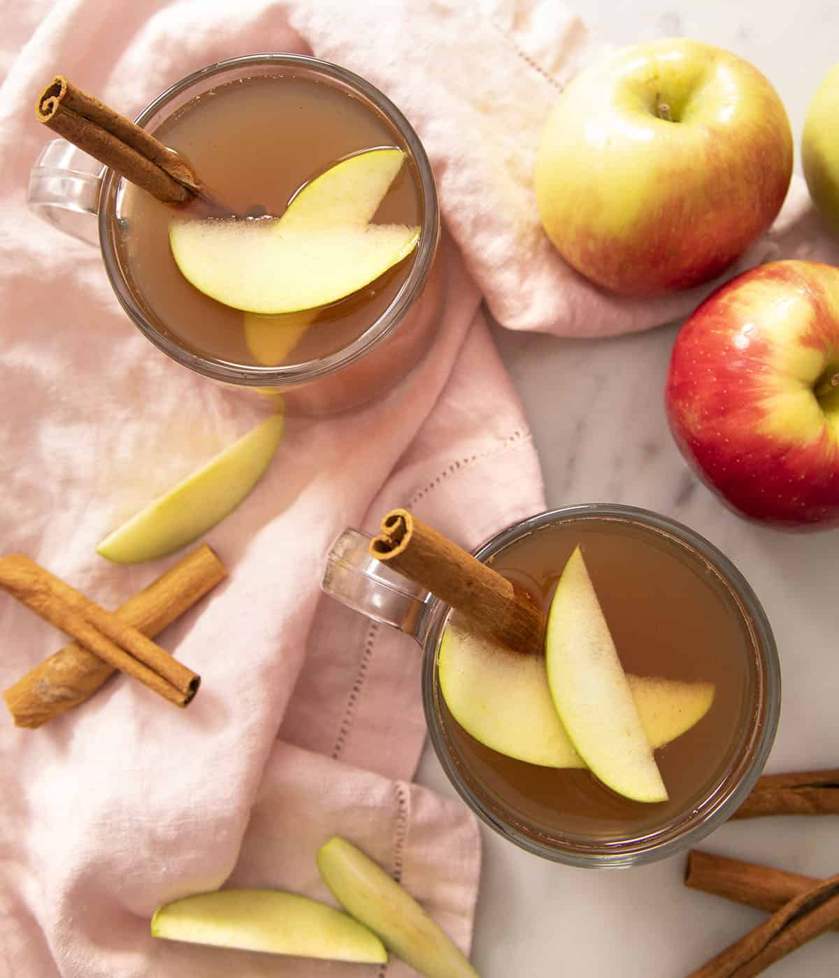 Two glasses of apple cider garnished with cinnamon sticks and apple slices on a marble counter..
