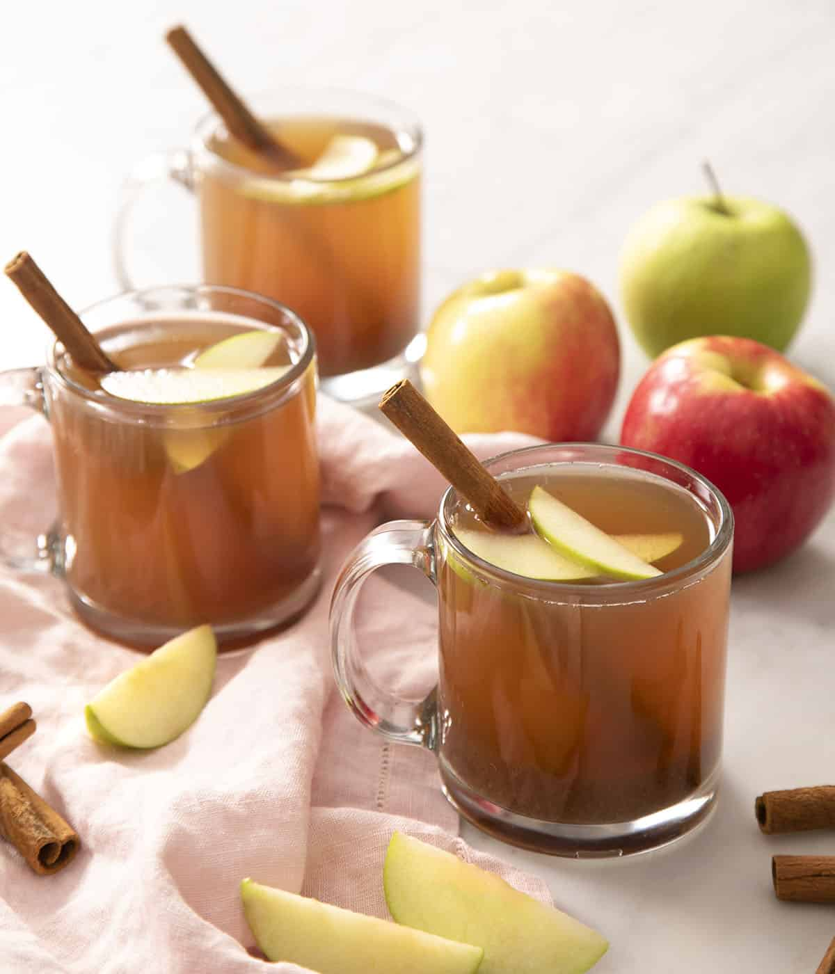 Three glasses of apple cider garnished with cinnamon sticks and apple slices.