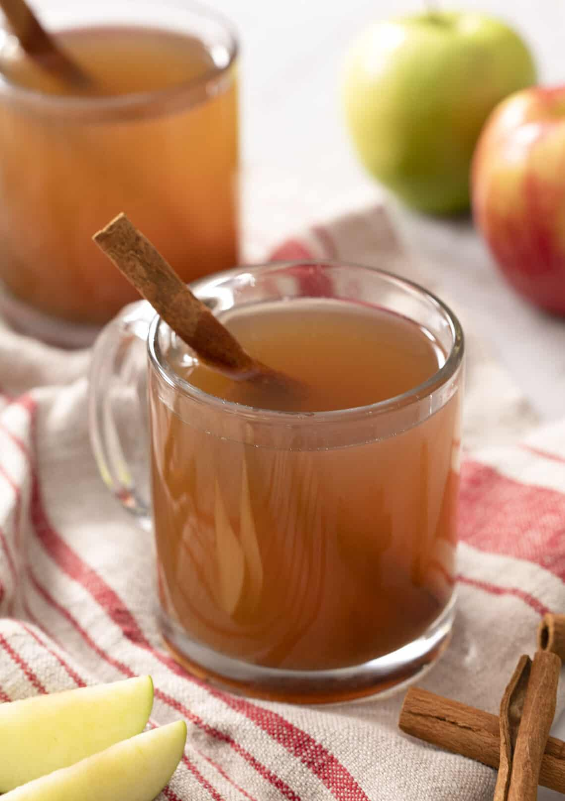 Two glasses of apple cider next to apples and cinnamon sticks.