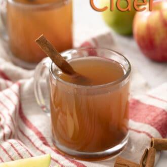 Two glass mugs of apple cider with cinnamon sticks.