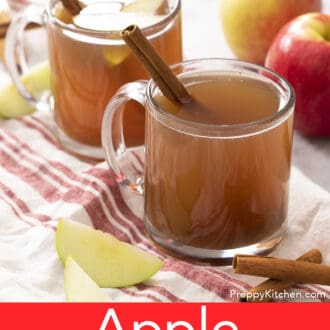 Two glass mugs of apple cider next to an apple.