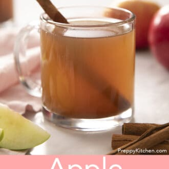 A glass mug of apple cider next to cinnamon sticks.