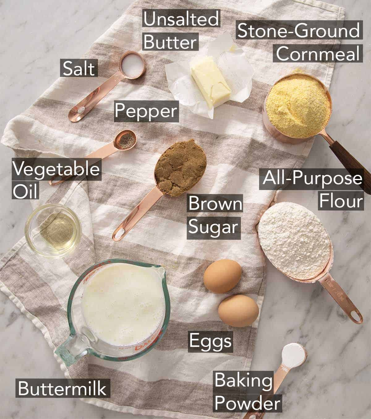 Ingredients to make cornbread on a marble counter.
