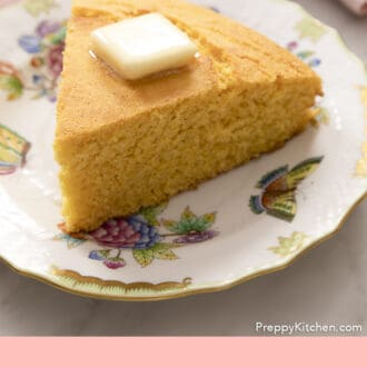 A wedge-shaped piece of cornbread topped with butter.
