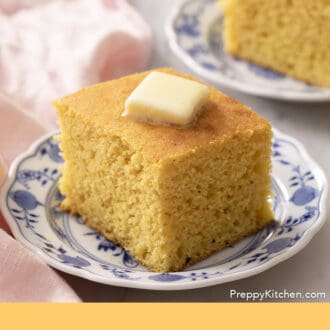 Two pieces of cornbread on small plates.