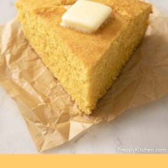 A wedge-shaped piece of cornbread on parchment paper.