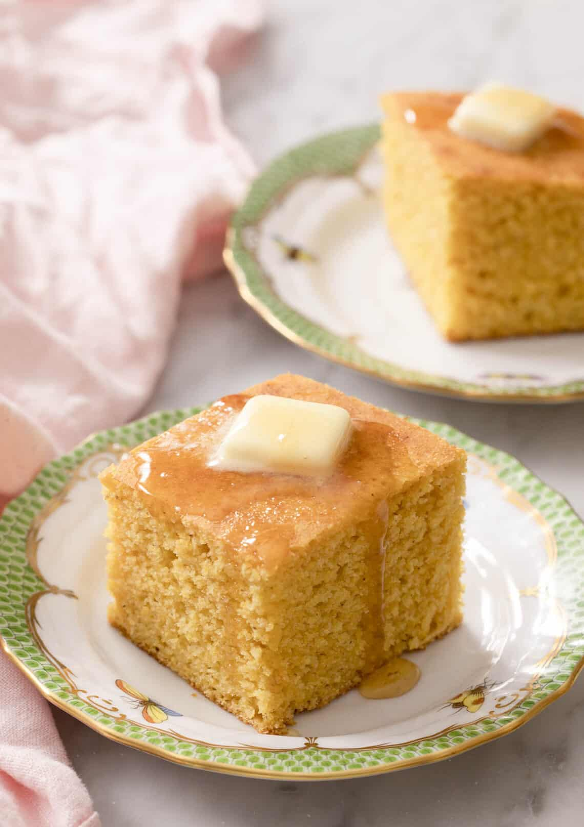 Pieces of cornbread topped with butter and honey on porcelain plates.