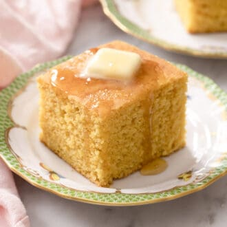 A square piece of cornbread topped with butter and honey.