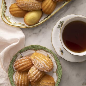 Madeleines next to tea on a marble counter.