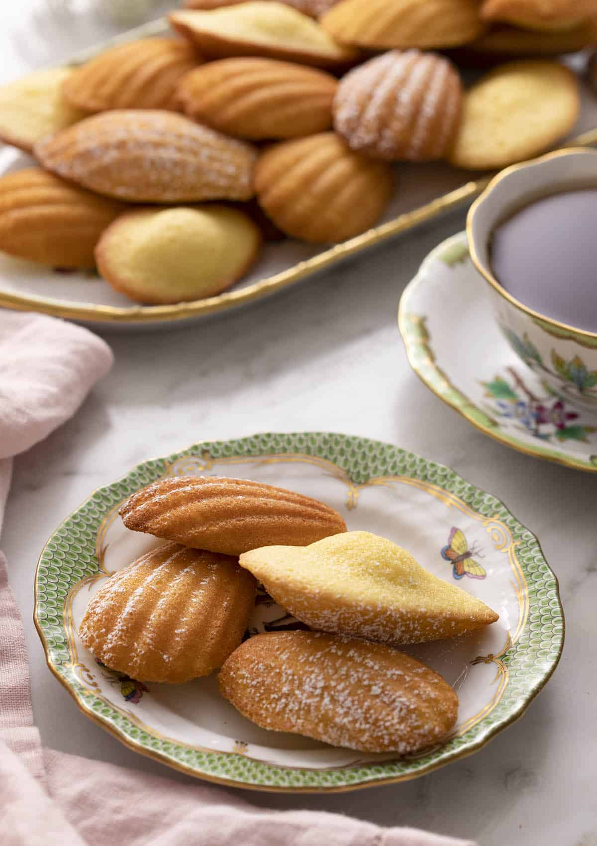 A green and white plate with Madeleines on a marble counter.