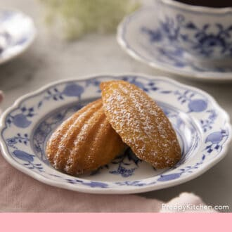 Two Madeleines next to a cup of tea.