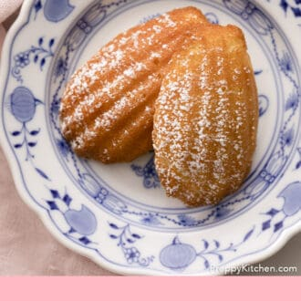 wo Madeleines dusted with powdered sugar on a blue and white plate.