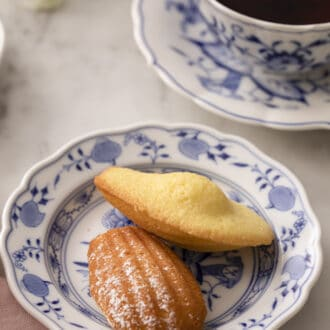 wo Madeleines on a blue and white plate next to a cup of tea.