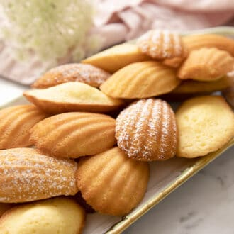 Madeleines on a tray next to a pink napkin.
