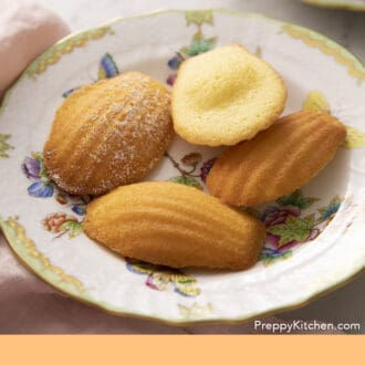 Four Madeleines on a plate next to a napkin.