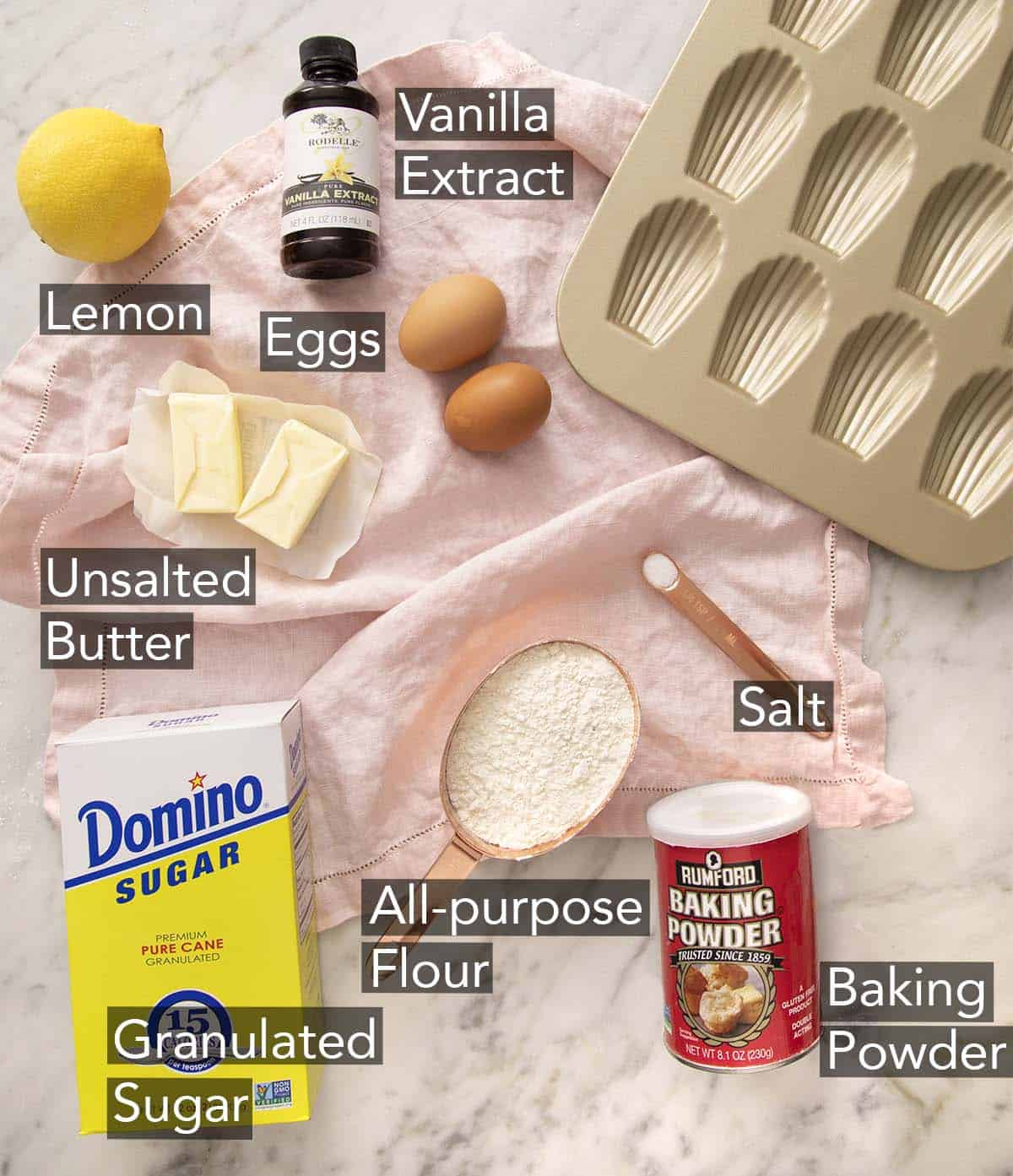 Ingredients to make Madeleines on a marble counter.