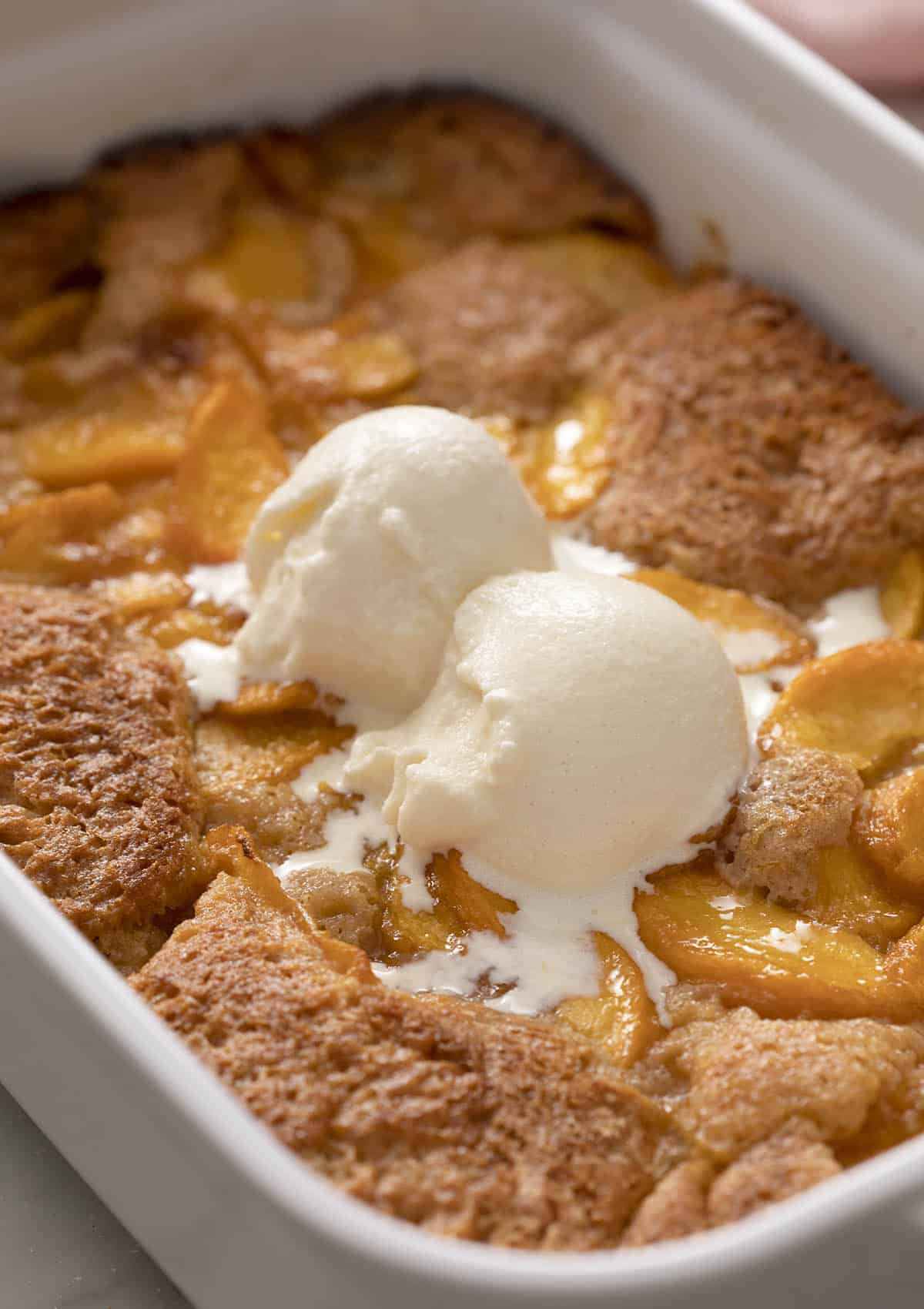 A delicious peach cobbler topped with two scoops of vanilla ice cream.