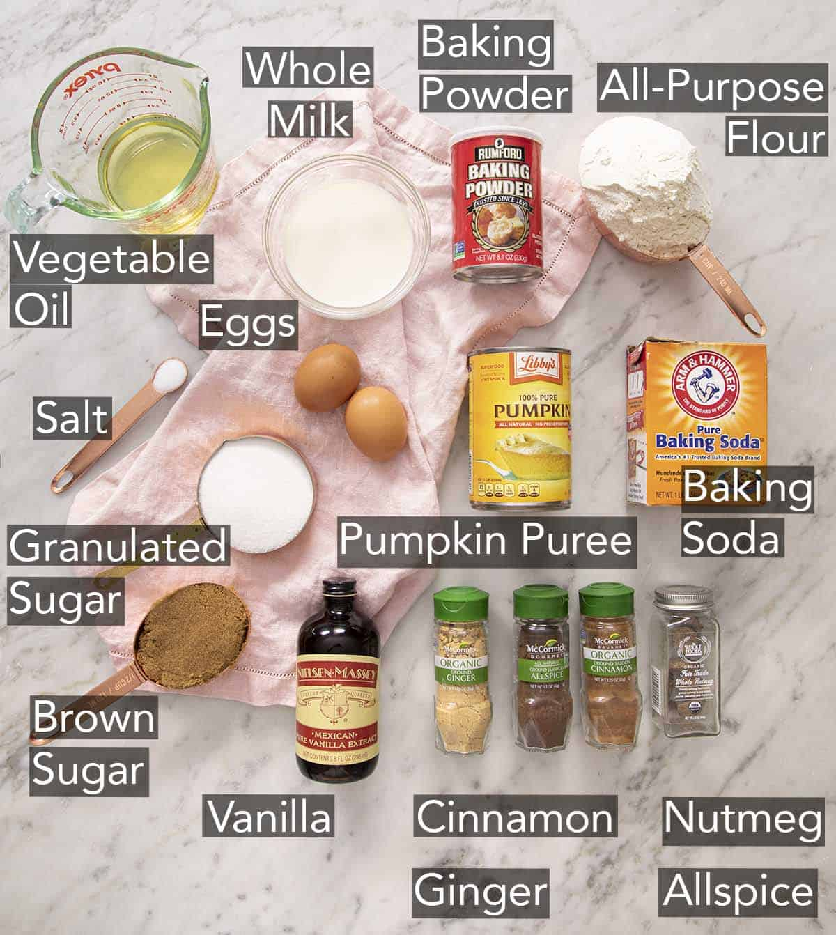 Ingredients to make pumpkin muffins on a marble counter.