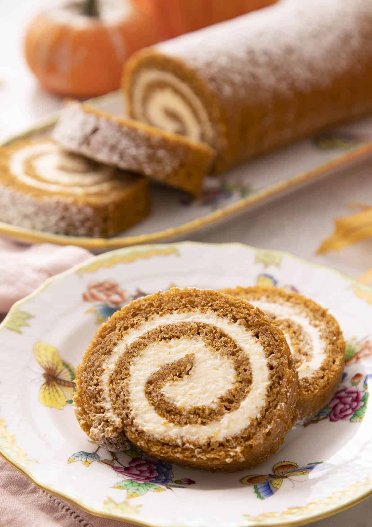Two pieces of a pumpkin roll cake on a plate.