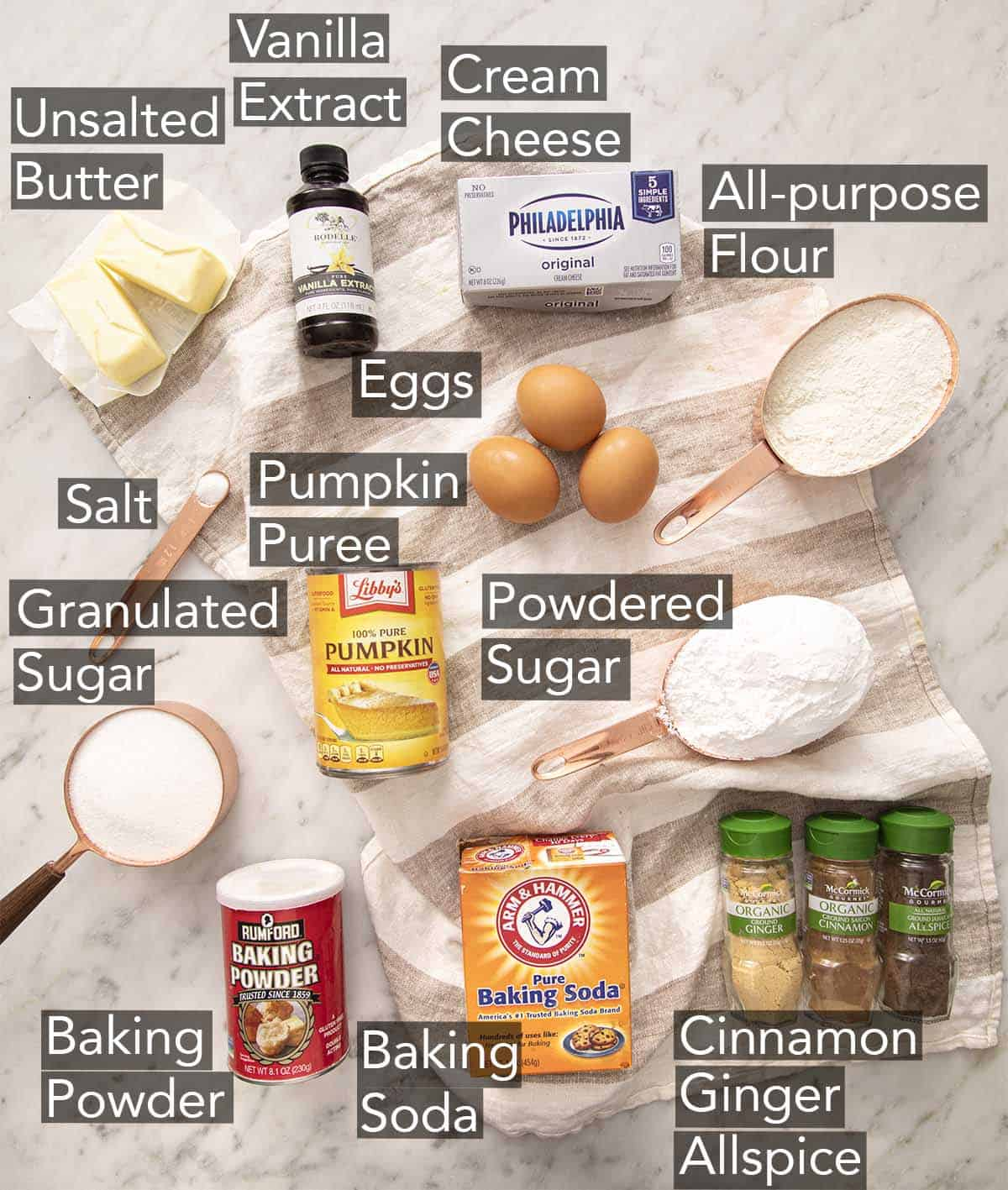 Ingredients to make a pumpkin roll cake on a marble counter.