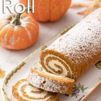 A pumpkin roll cake next to two pumpkins.