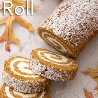 A pumpkin roll cake next to some fall leaves.