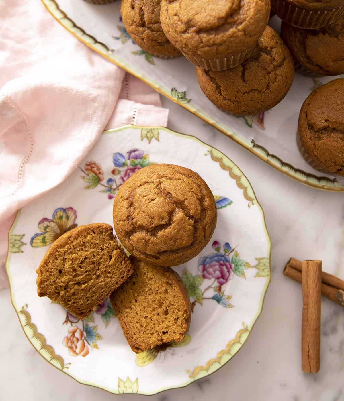 A top-down photo of pumpkin muffins on porcelain serving ware.