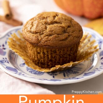 A pumpkin muffin on a plate with the paper wrapper peeled off.