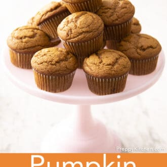 A pink cake stand filled with pumpkin muffins.