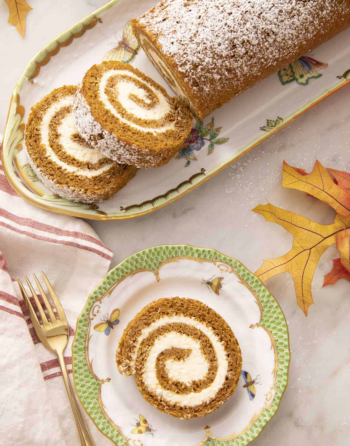 A piece of a pumpkin roll cake on a green and white plate.