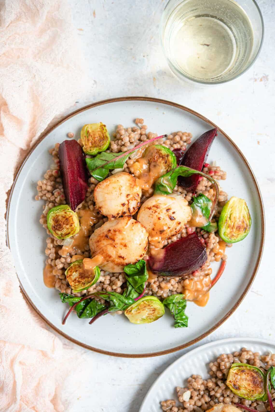 An overhead shot of 3 sauteed scallops on a plate with cous cous and veggies