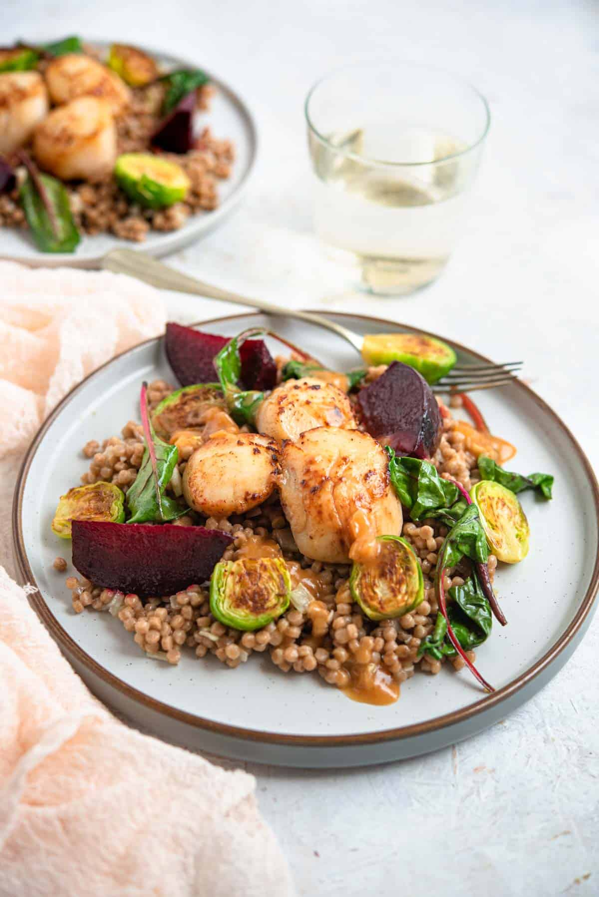 A side shot of sauteed scallops on a plate with cous cous and veggies