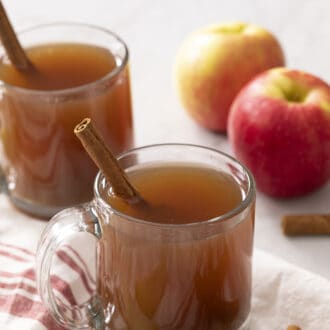 Two glass mugs of apple cider on a counter.