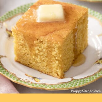A piece of cornbread on a green and white plate.