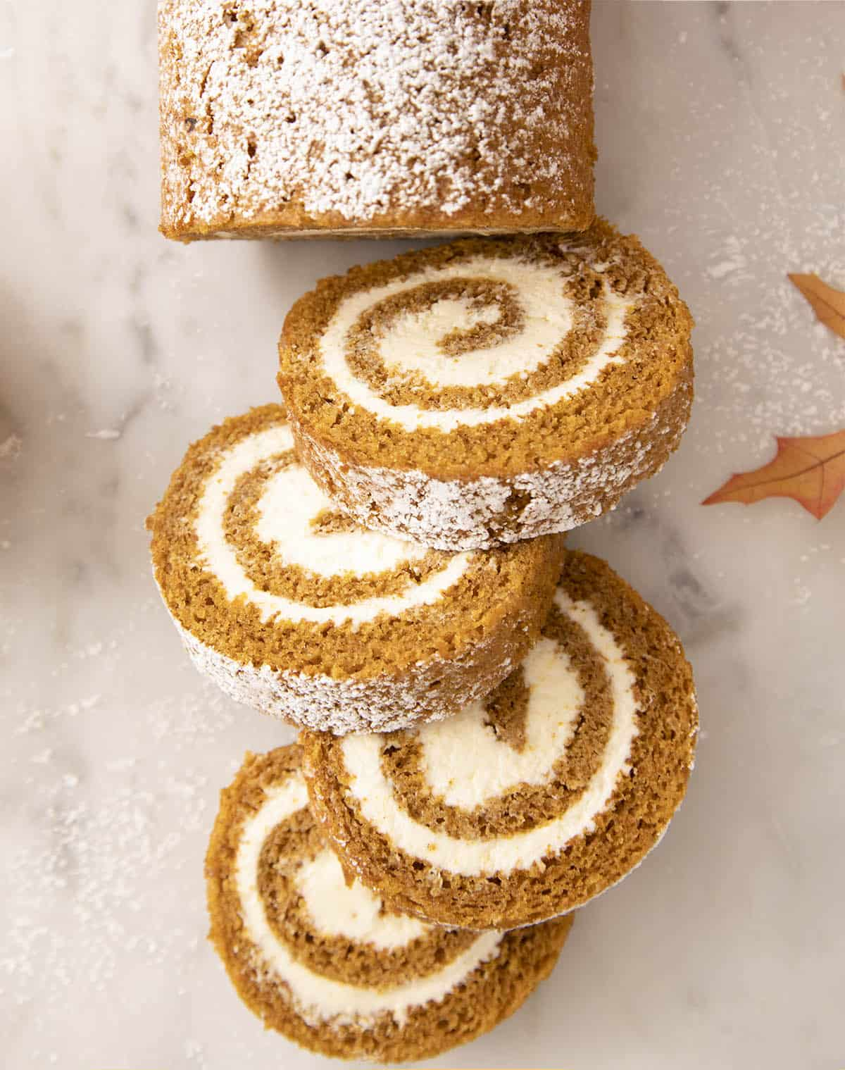 Pieces of pumpkin roll cake on a marble counter.