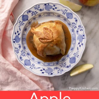 An apple dumpling on a blue and white plate next to some apple pieces.