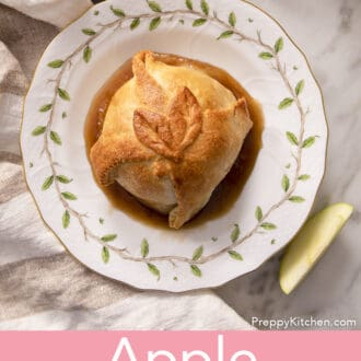An apple dumpling on a white plate with brown sugar syrup.