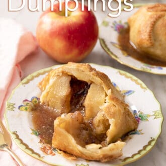 An apple dumpling that has been cut in half on a plate.