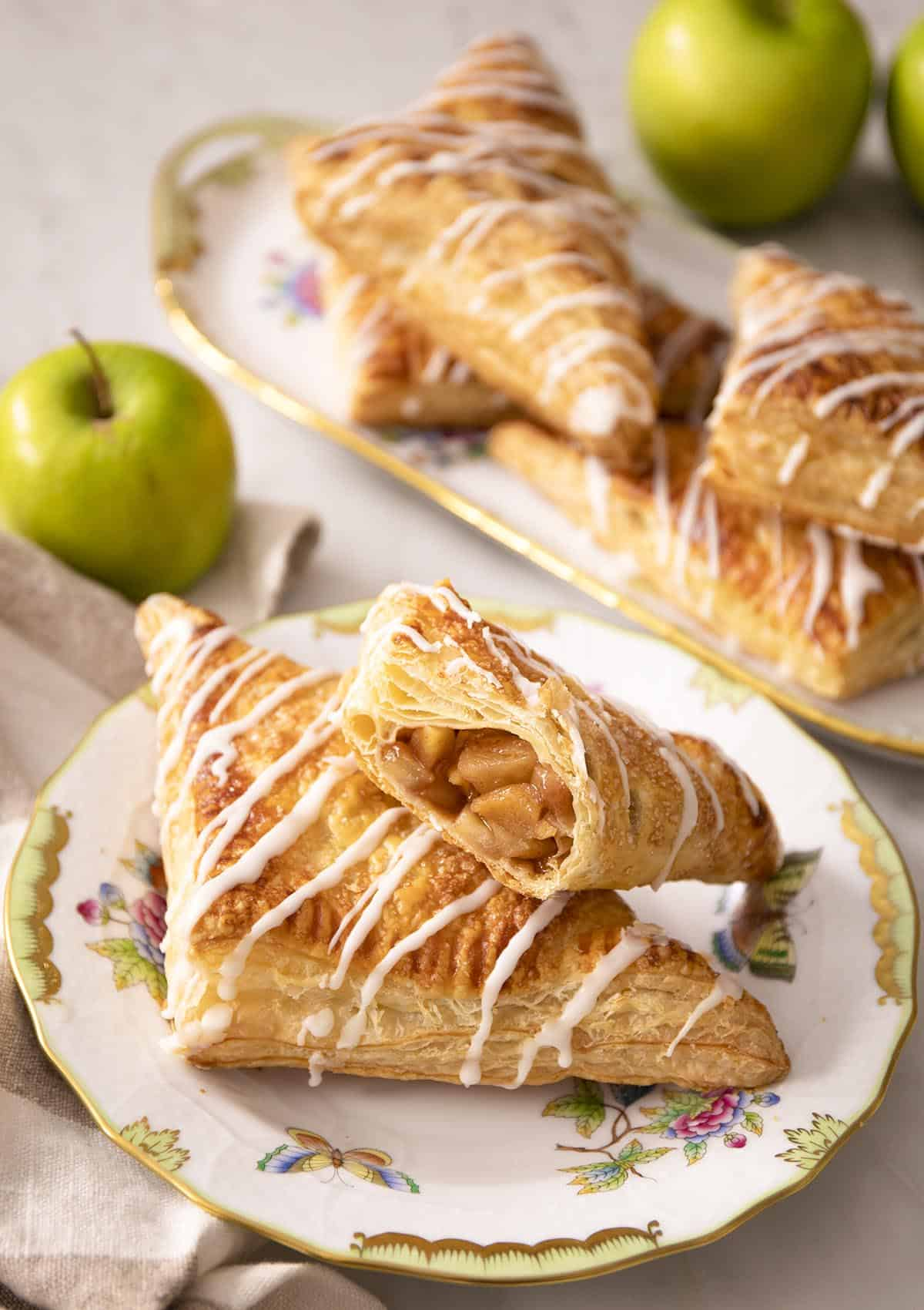 Apple turnovers on a porcelain plate next to green apples.