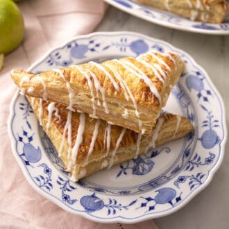 Two apple turnovers on a blue and white plate.