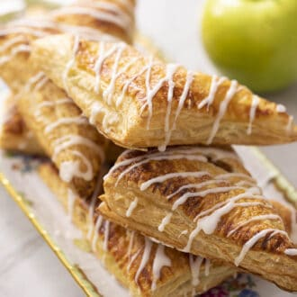 A stack of apple turnovers next to a green apple.