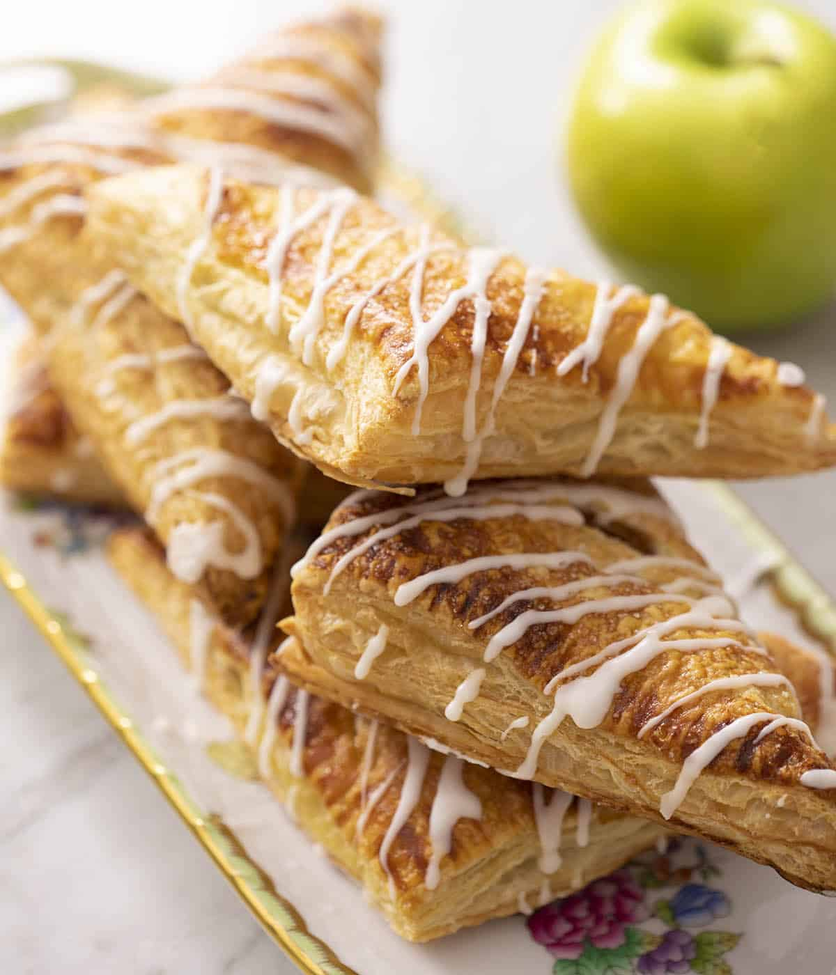 Flakey apple turnovers on a serving tray.