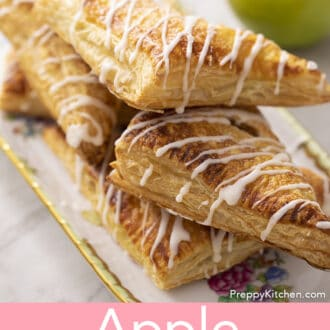A stack of apple turnovers on a porcelain tray.