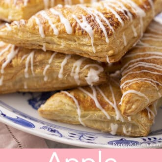 Apple turnovers drizzled with glaze on a serving platter.