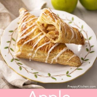 Two apple turnovers on a plate with one having a bite taken out.