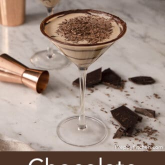 A chocolate martini next to a copper jigger and broken pieces of chocolate.