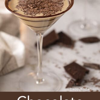 A chocolate martini garnished with shaved chocolate on a marble table..