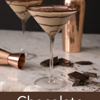 Two chocolate martinis with a swirls of chocolate syrup on a marble counter.